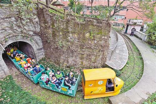 /北碚区实验幼儿园的孩子们在校园内乘坐小火车。记者万难摄