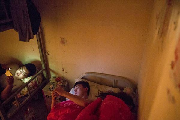 2016年4月10日,北京,由于当天宵夜太晚,周文才与妻子挤在宿舍单人床上凑合一夜。 澎湃新闻记者徐晓林图